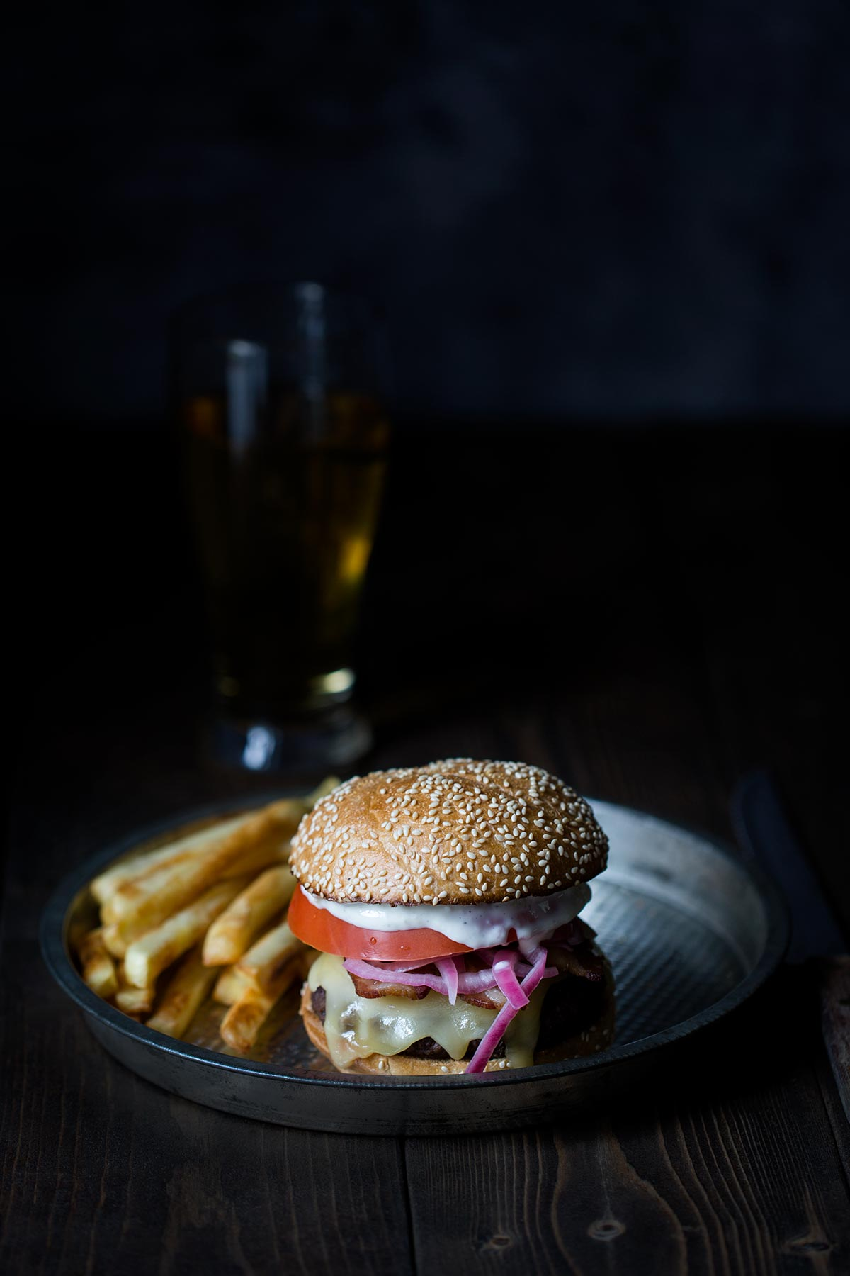 A burger topped with raclette cheese, pickled shallots, tomato, and aioli.