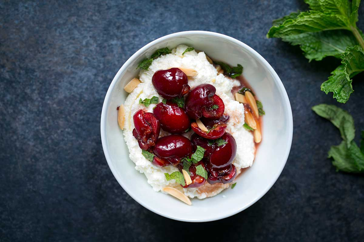 A macerated cherries recipe in a bowl with ricotta cheese, almonds and mint.