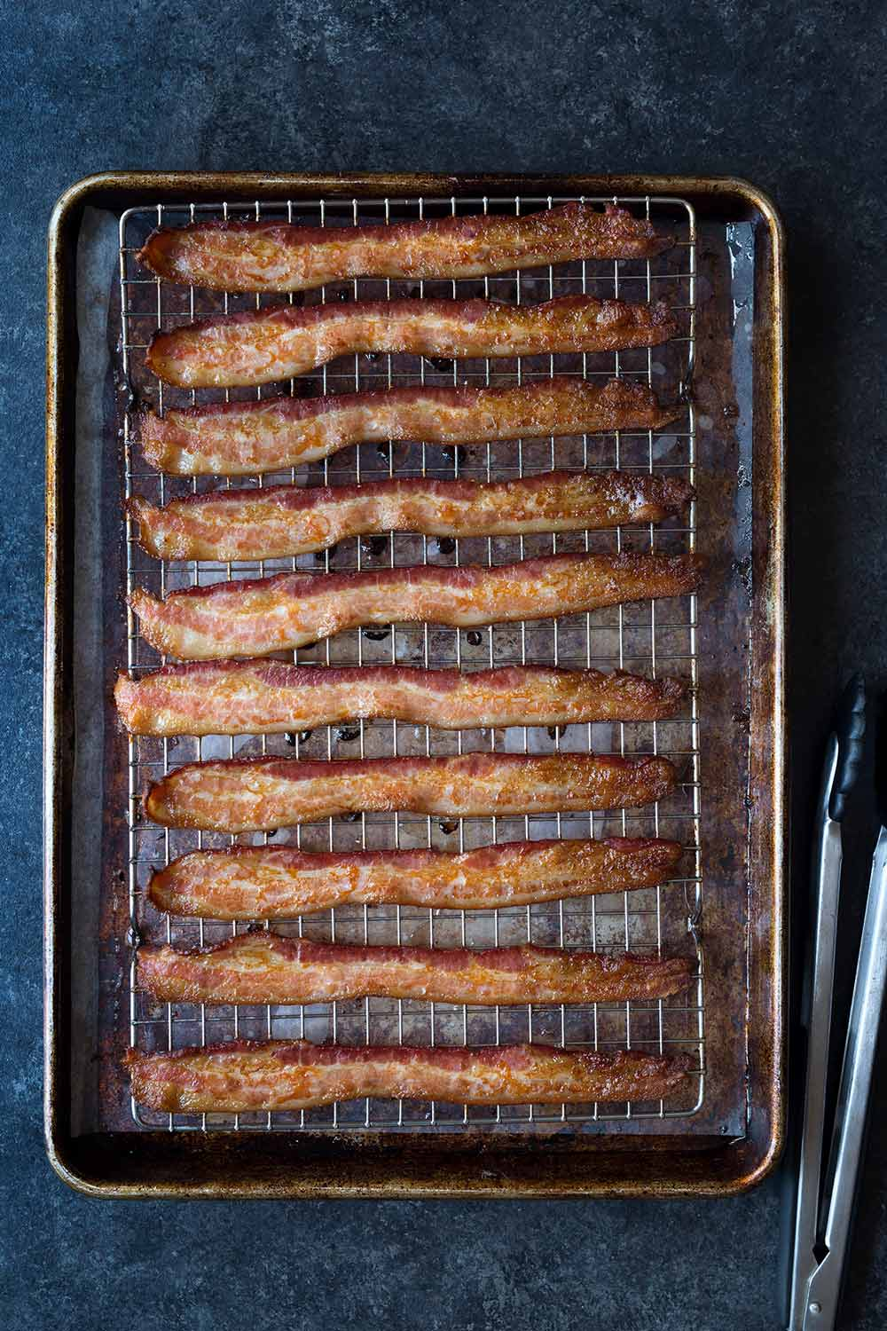Oven-baked bacon on a sheet pan and wire rack. Photo shows overhead shot of finished bacon on the sheet pan and tongs on a blue backdrop.