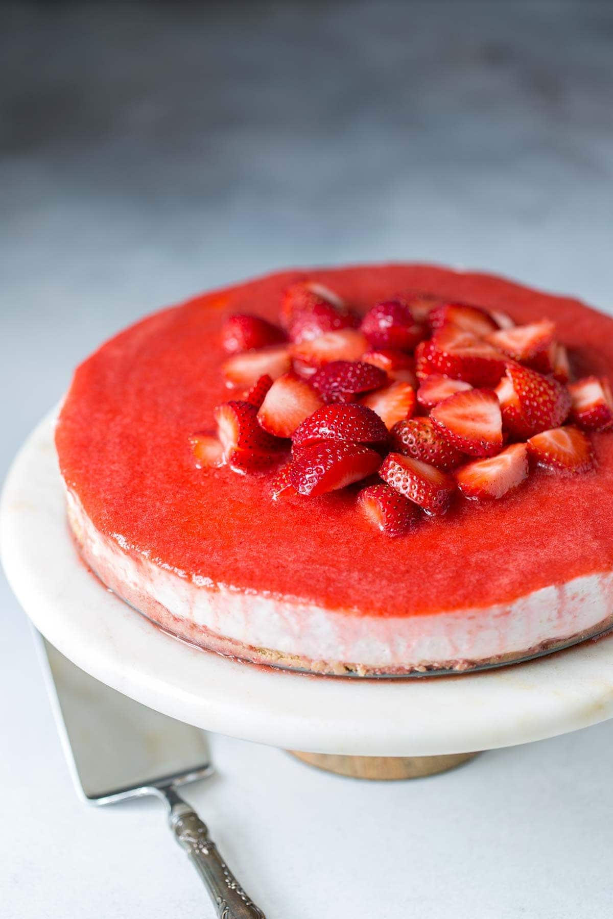 Strawberry No-Bake Cheesecake showcased on a marble and wood cake stand with a silver cake slicer.