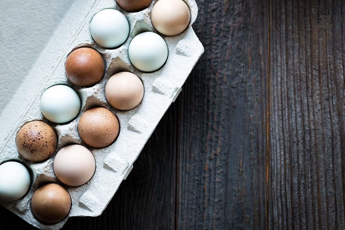 Multi-colored farm eggs in a carton.