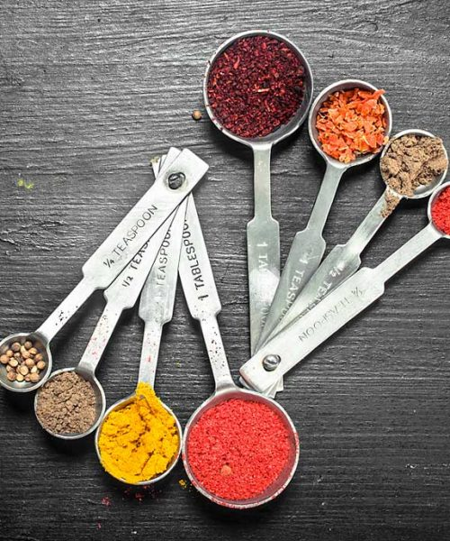 Two sets of measuring spoons filled with various colorful spices, set on a dark backdrop. Learn how many teaspoons are in a tablespoon.