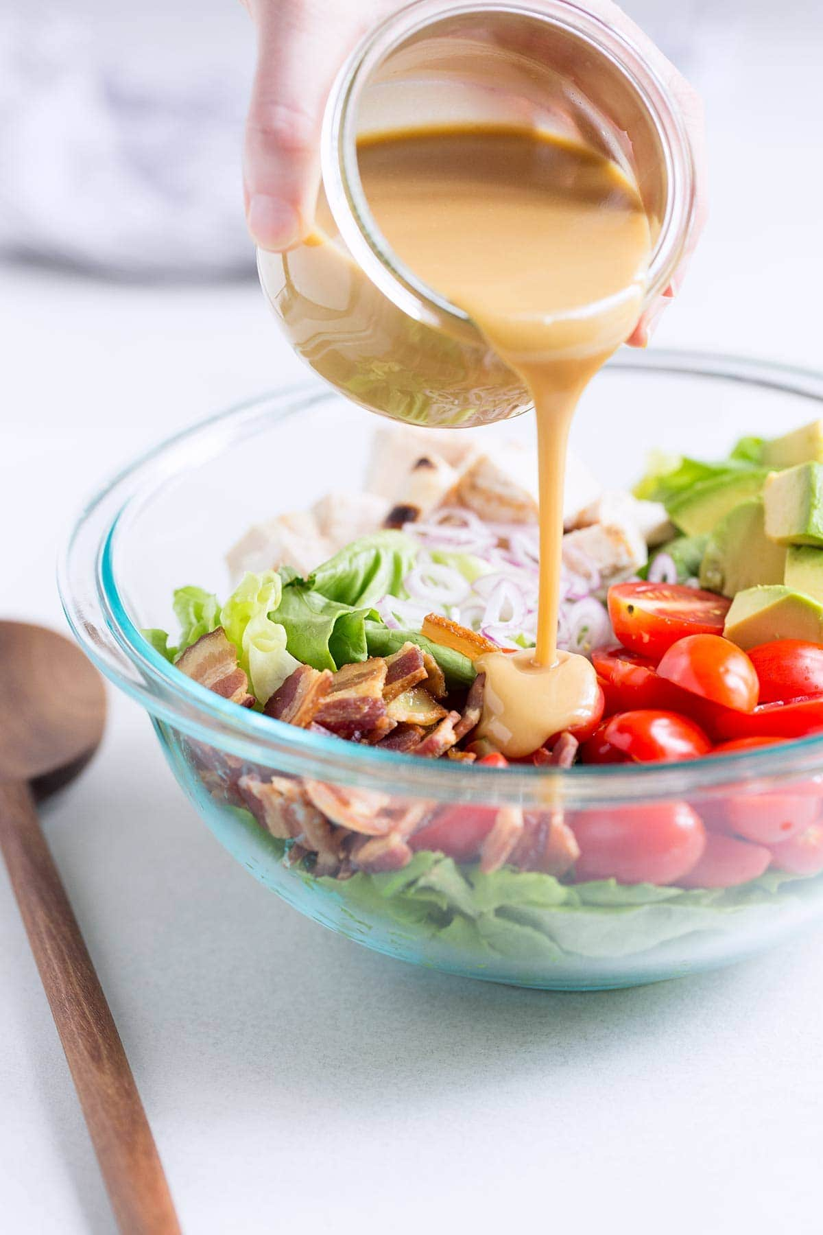 A side angle photo of honey mustard dressing being poured onto chicken bacon avocado salad