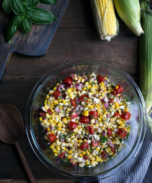 Summer corn salad recipe in a large bowl, surrounded by fresh corn and basil.