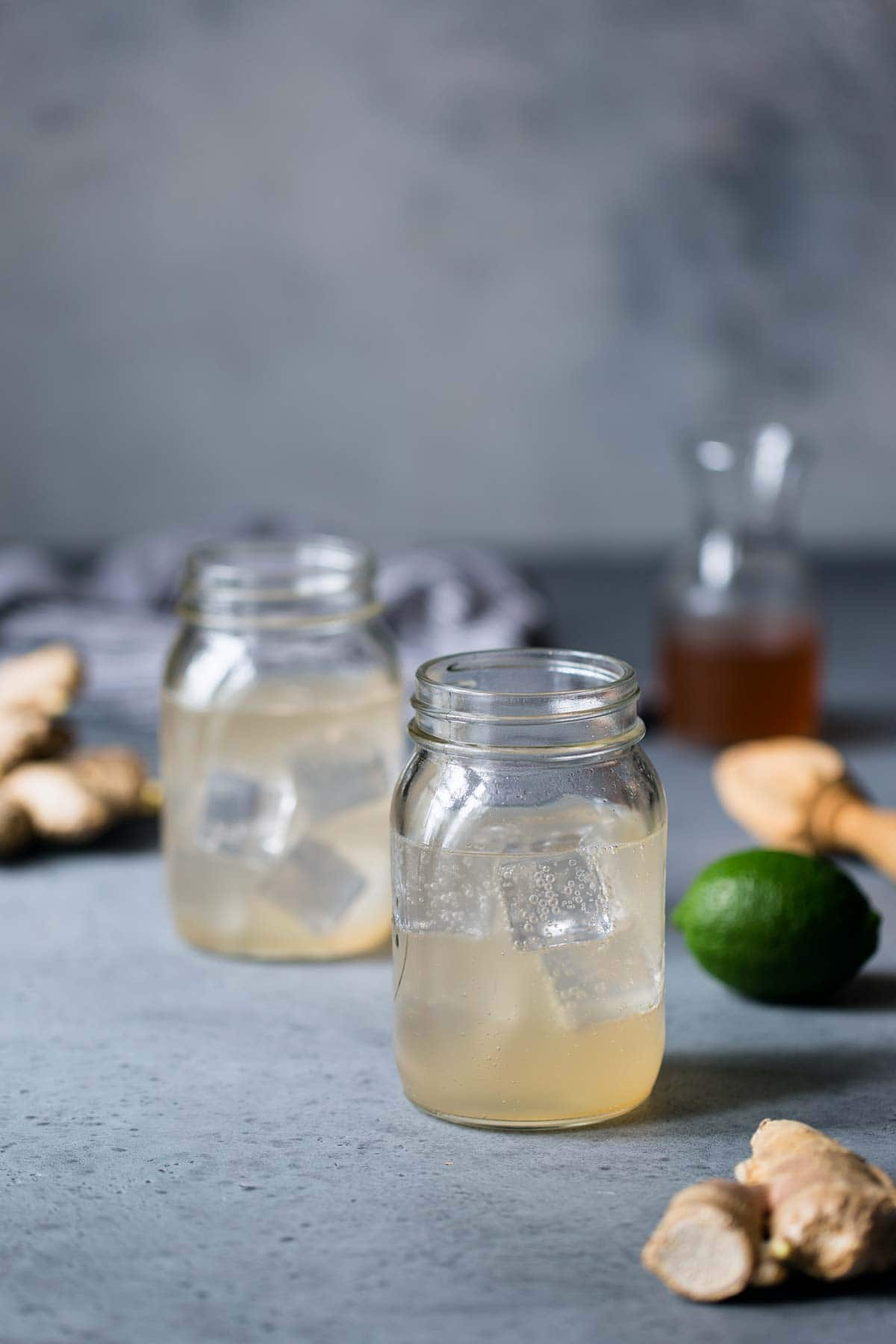 Two mason jars filled with homemade ginger ale, surrounded by homemade ginger syrup, limes and fresh ginger