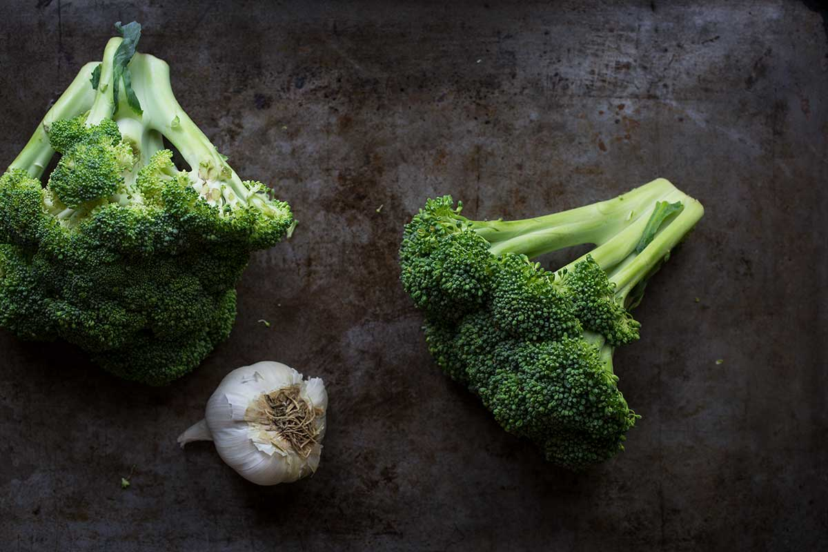 Raw broccoli and a whole head of garlic on a sheet pan