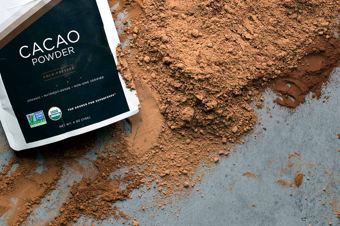 A bag of raw cacao powder on top of the cacao powder itself.