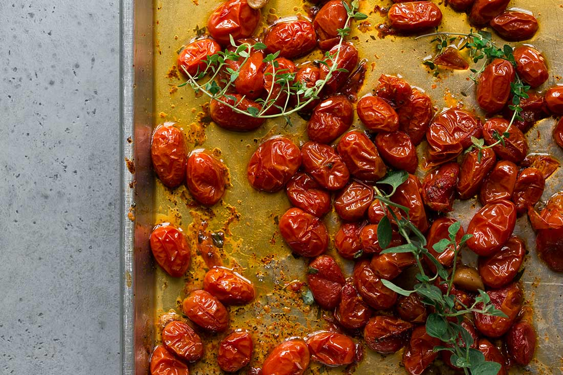 Roasted grape tomatoes, fresh herbs, and infused olive oil on a sheet pan.