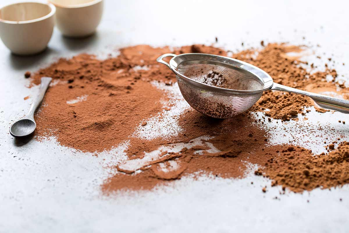 A small fine mesh strainer sitting over cocoa powder that has been sifted