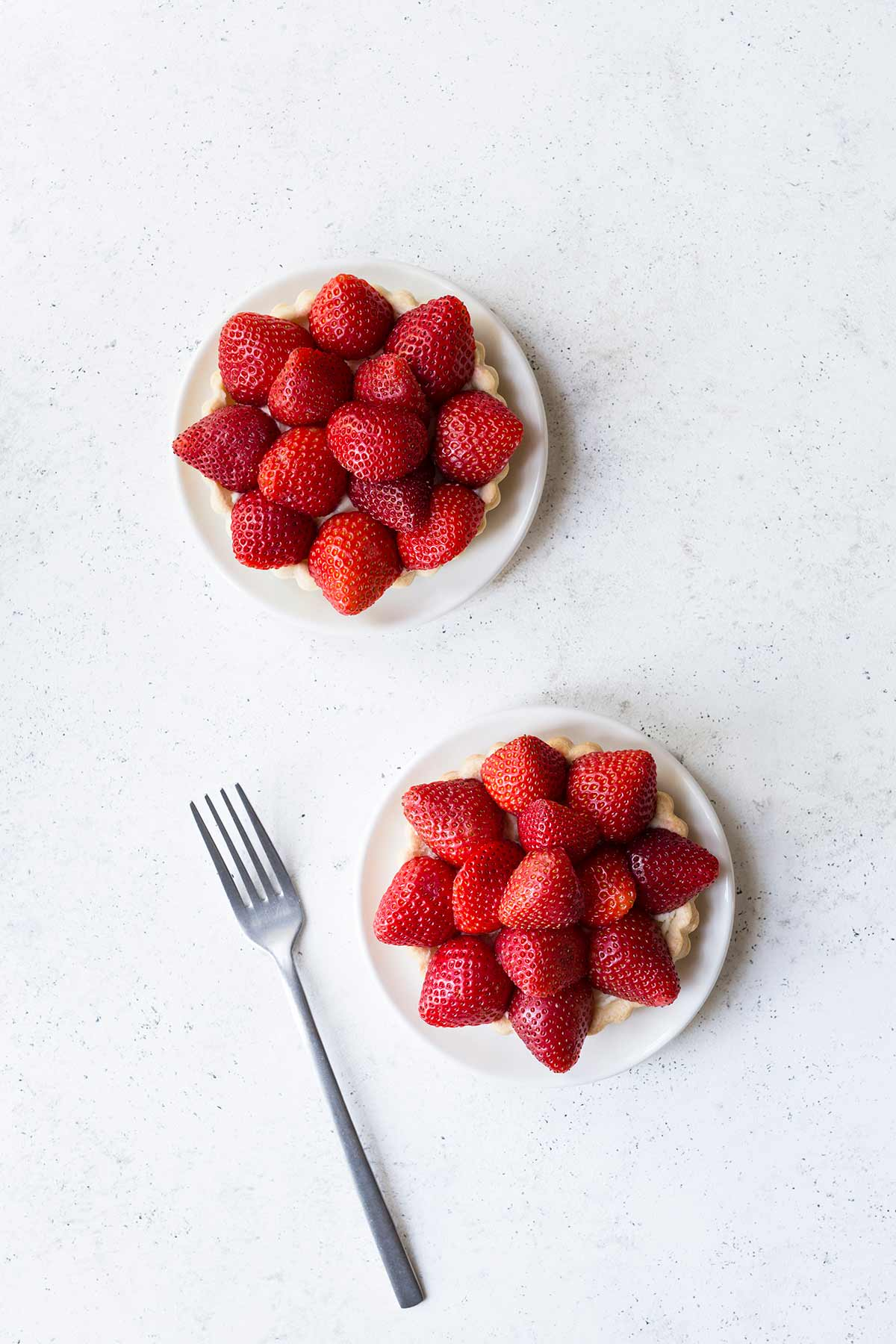Two strawberry tarts on white plates on a pale backdrop.