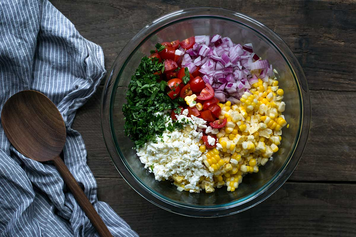 Unmixed ingredients for corn tomato salad in a bowl, including red onions, basil, feta, corn and tomatoes.