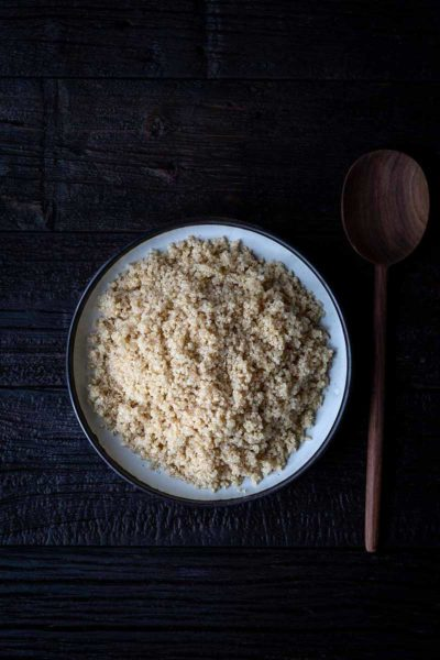 cooked quinoa in a large white bowl next to wooden serving spoon