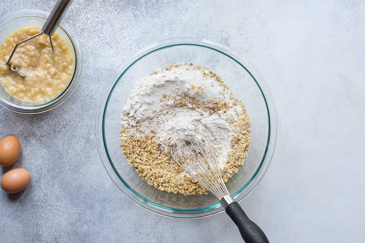 Ingredients for banana nut bread in a bowl with a whisk.
