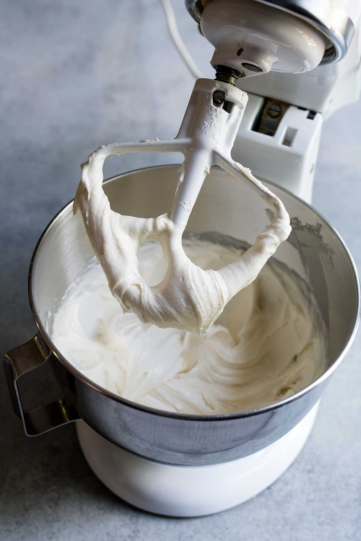 A Kitchen Aid stand mixer fitted with the paddle attachment lifted to show the finished cream cheese frosting.