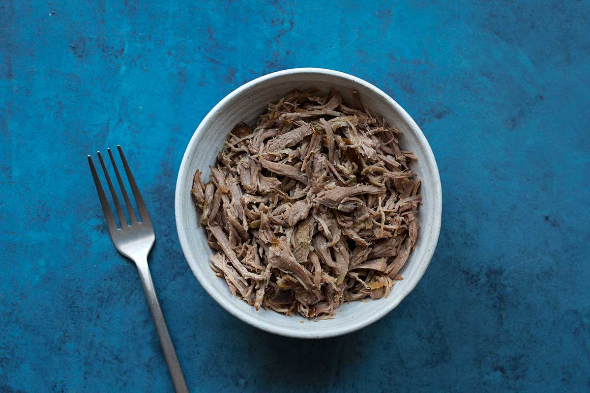 Slow cooker pulled pork in a bowl with a fork