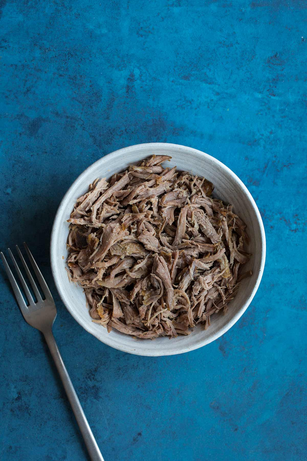 Slow cooker kalua pig in a bowl with a fork on a blue backdrop