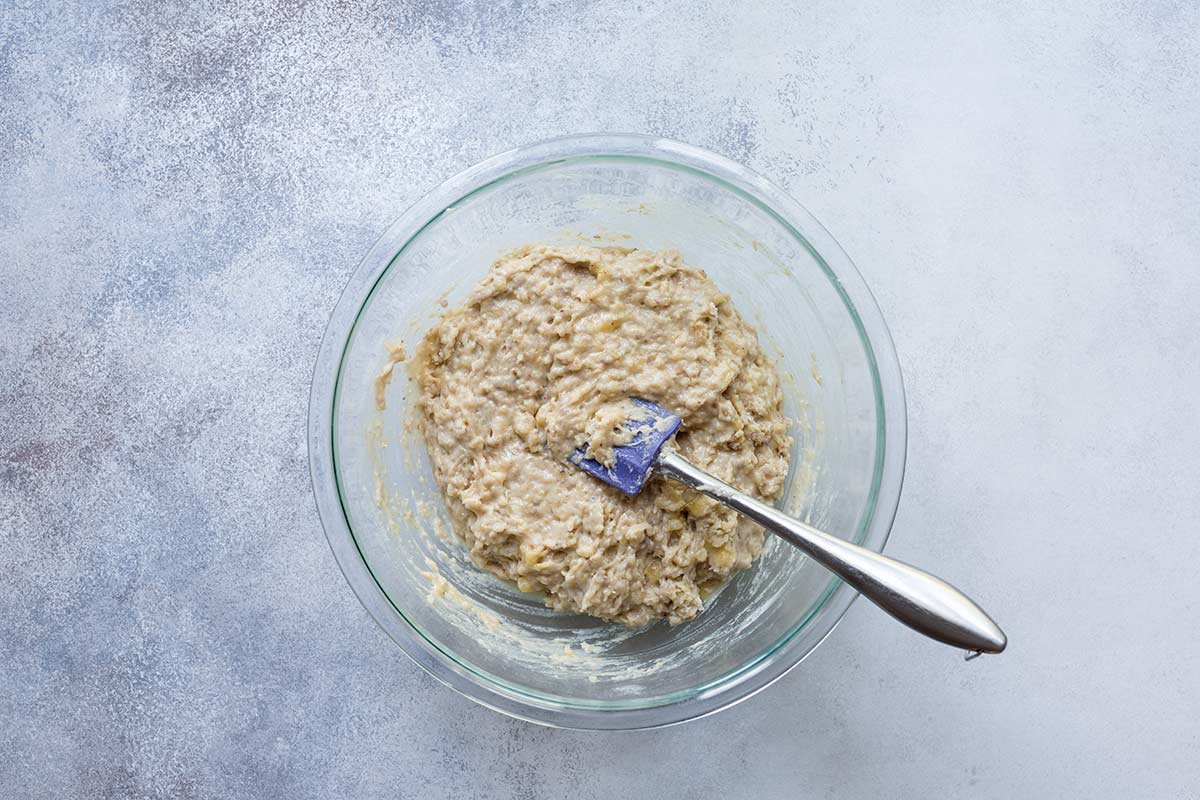 Raw ingredients for banana bread being stirred with a spatula in a pyrex bowl.