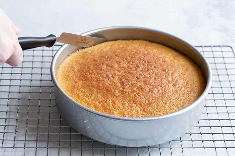 running an offset spatula around the edge of a baked yellow cake