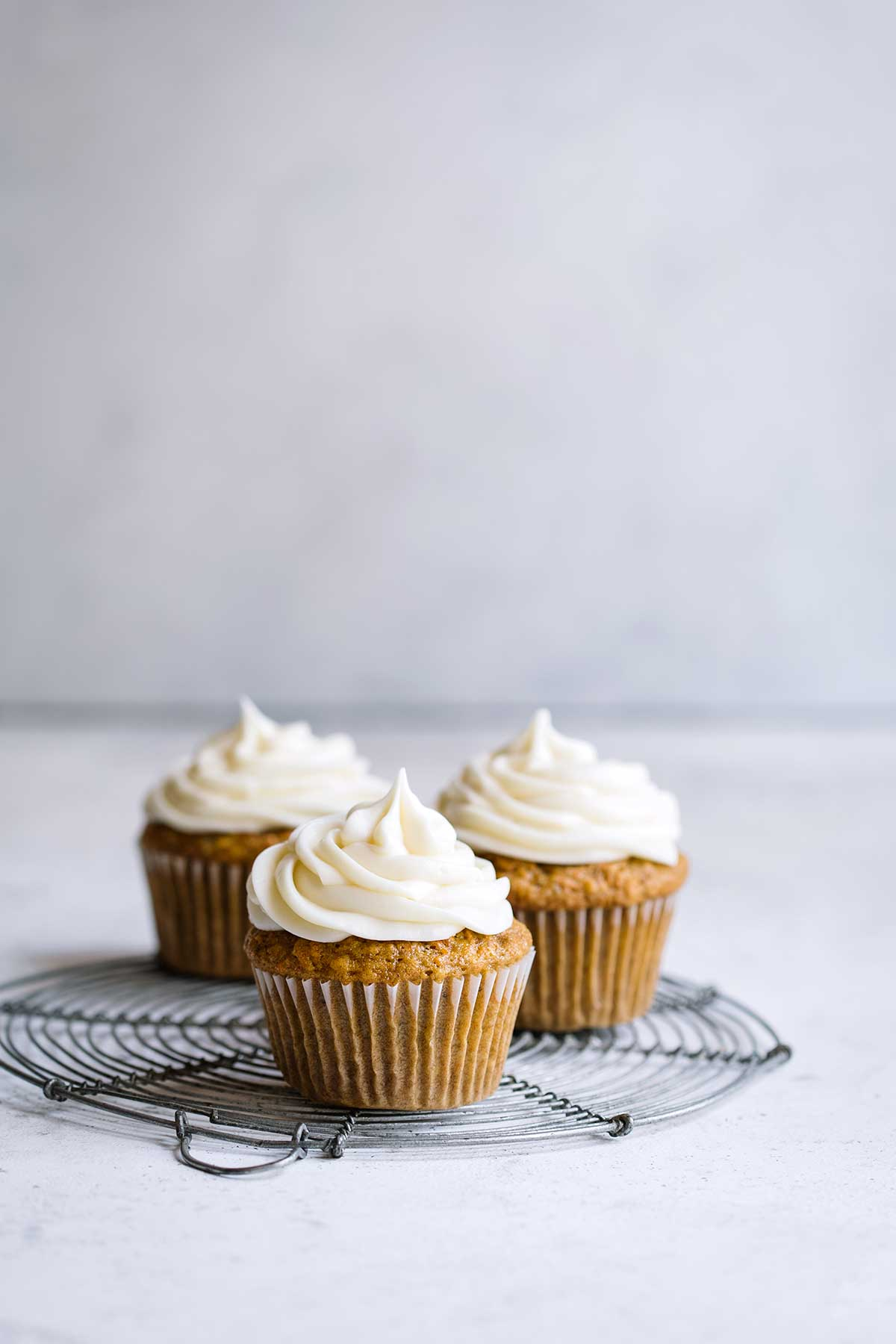 Carrot Cake Cupcakes on a pale backdrop
