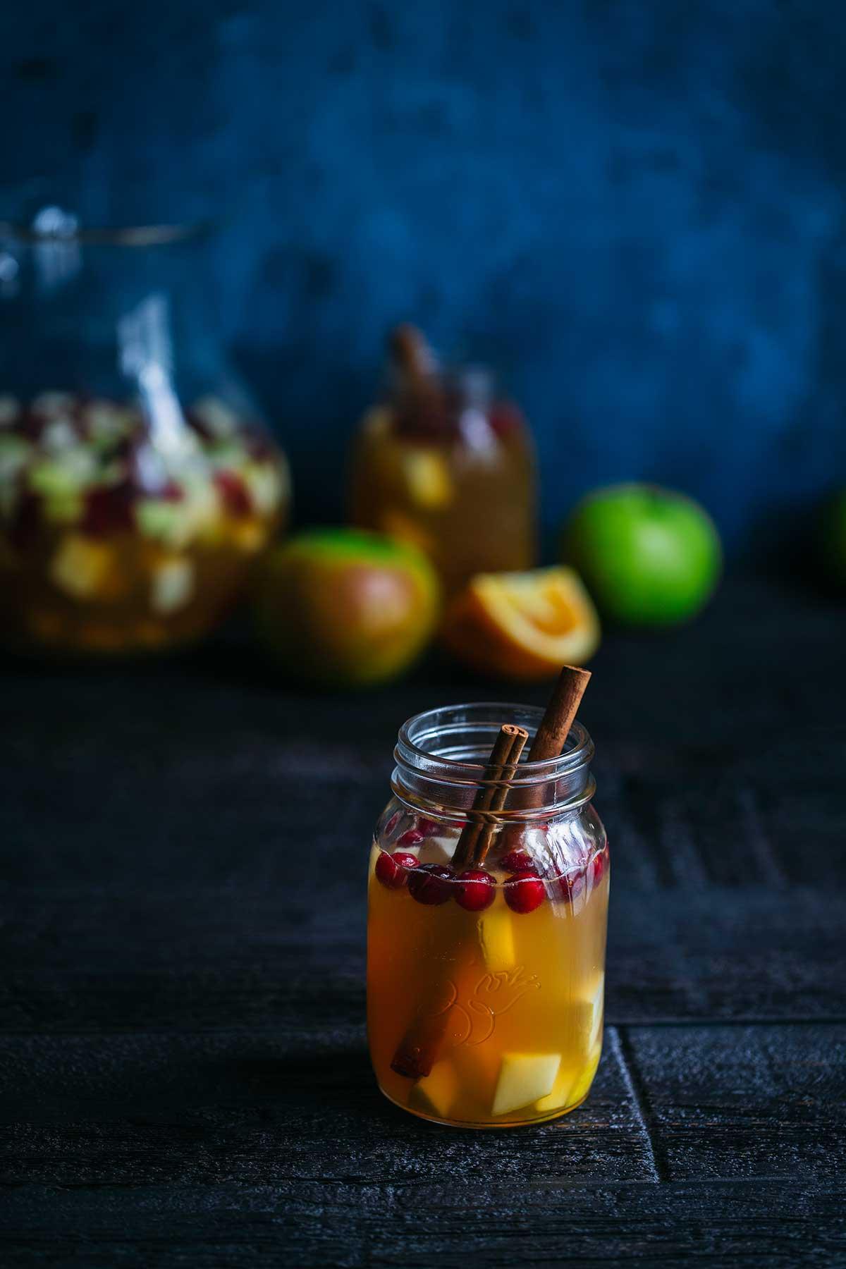 Apple cider sangria in a mason jar, garnished with cinnamon sticks