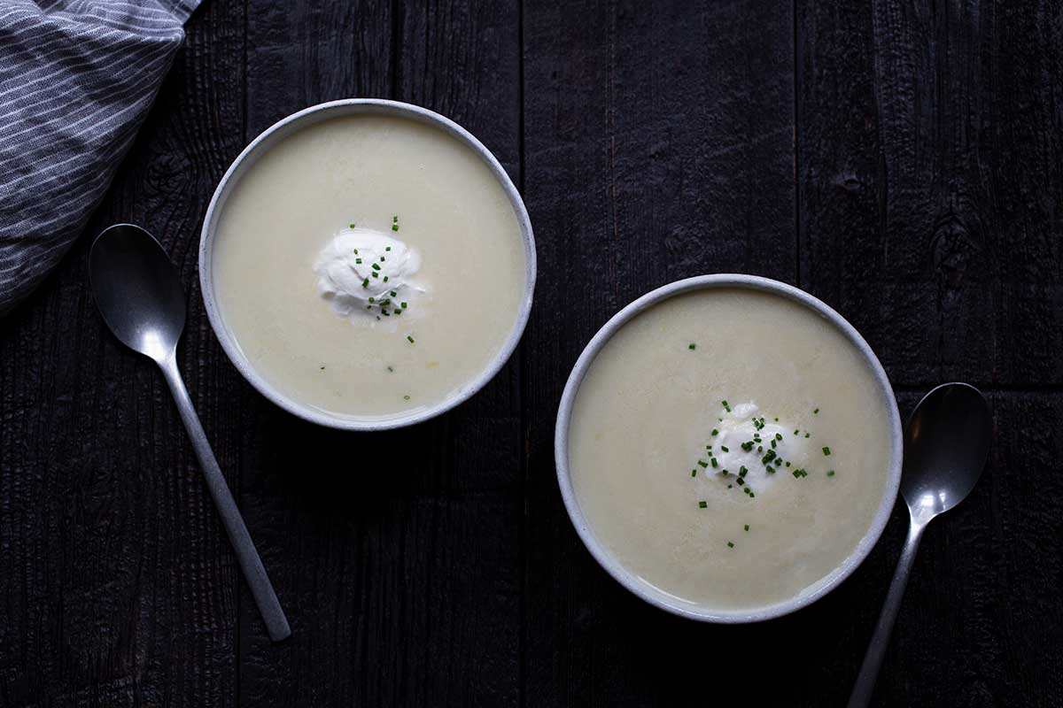 Two bowls of potato leek soup topped with soup cream and chives. Two spoons and a napkin included in photo.