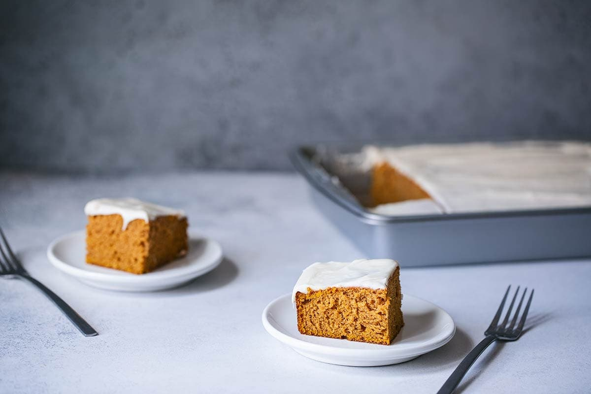 Two slices of pumpkin cake next to the remaining unsliced cake.