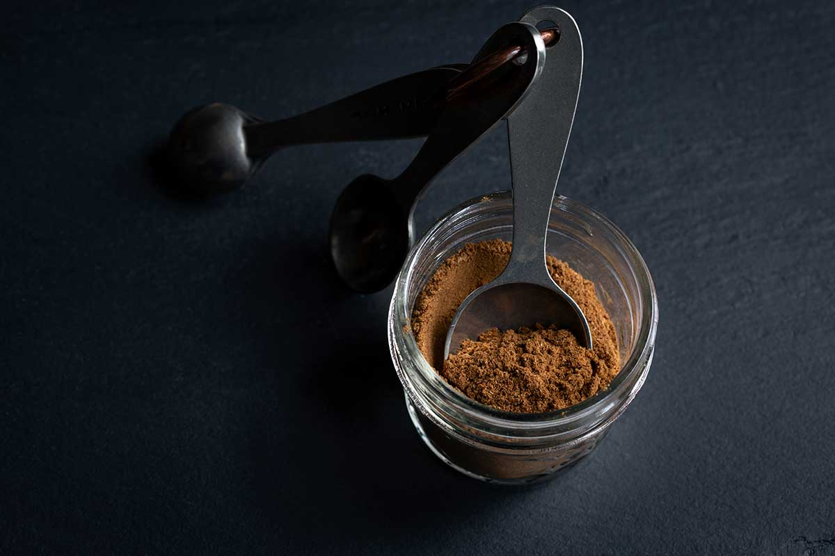 Homemade Pumpkin Pie Spice Recipe in a mason jar with measuring spoons