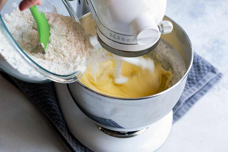 adding dry ingredients to bowl of standing mixer