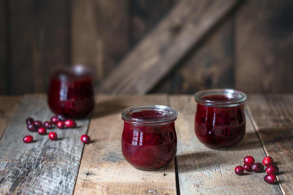 Cranberry orange sauce in mason jars, surrounded by cranberries