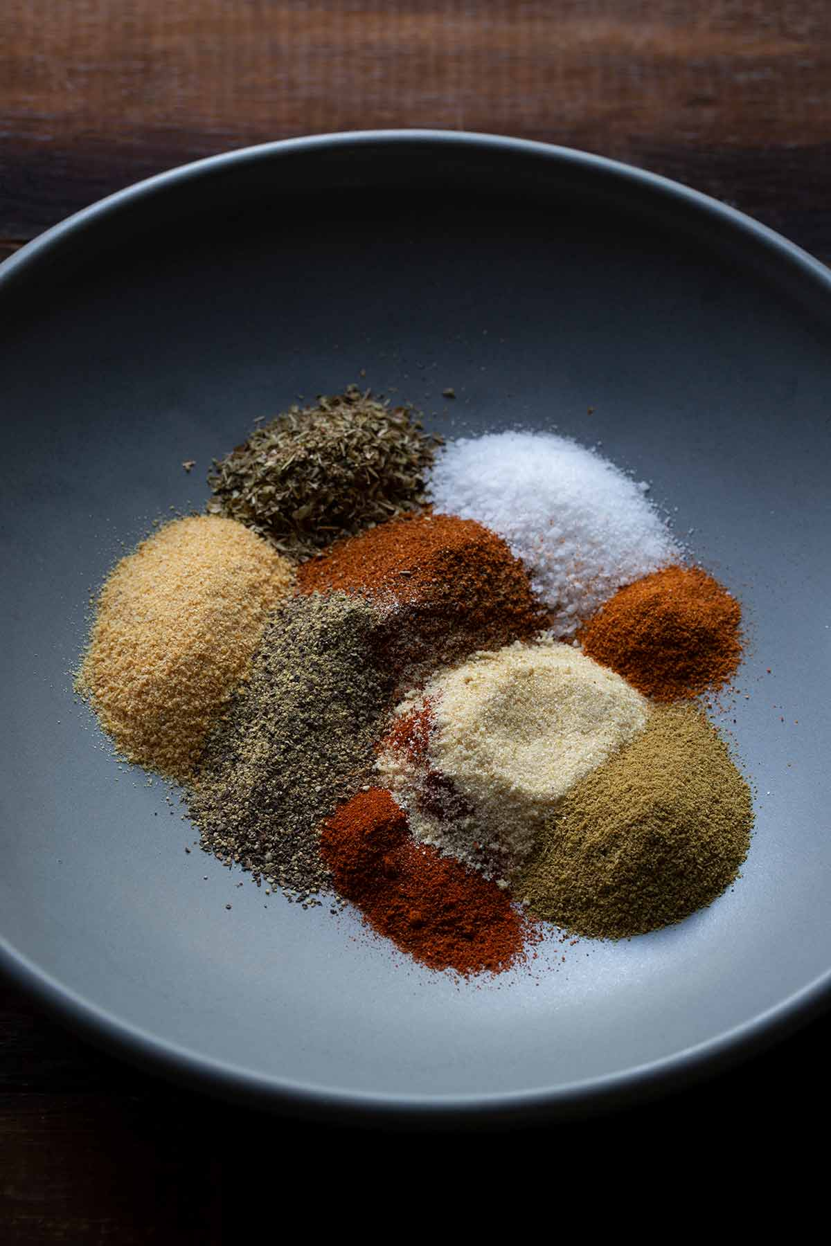 Various spices for taco seasoning spread out on a plate.
