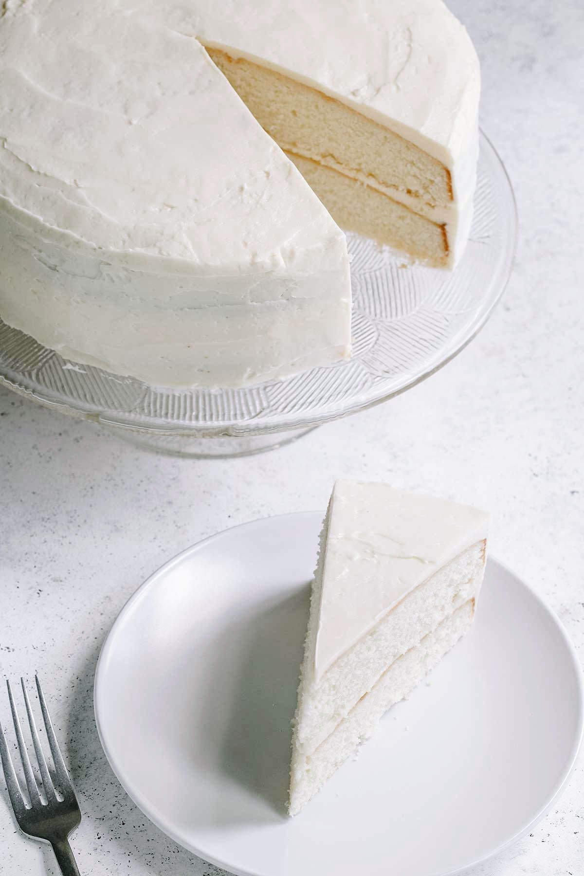 Classic Homemade White Cake on cake stand with piece of cake on white plate