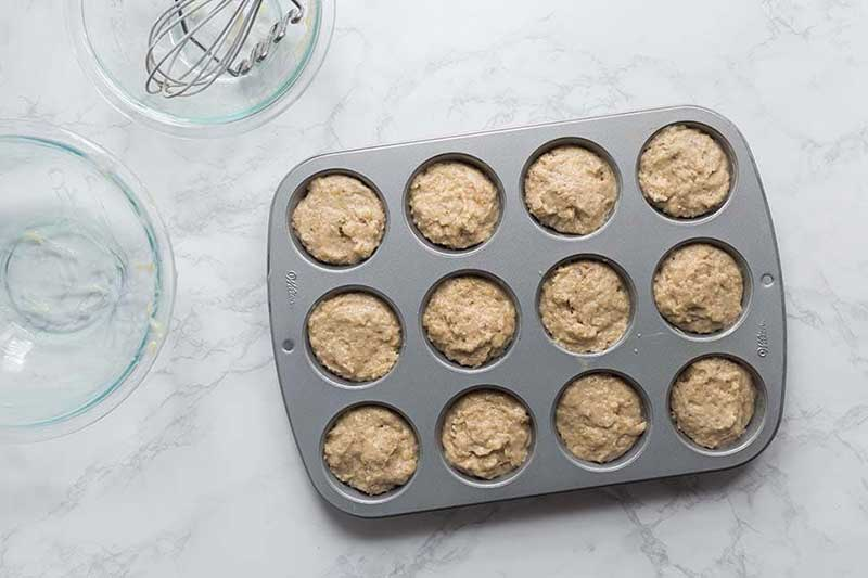 Filling banana muffin batter about 2/3 full in pan