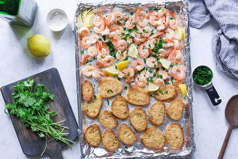 Sheet pan topped with cooked shrimp and bread