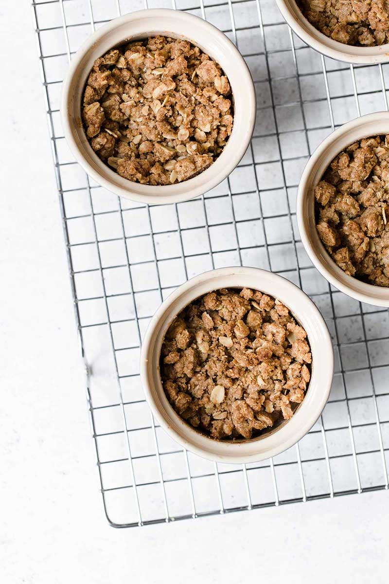 4 apple crumbles in ramekins sitting on a cooling rack