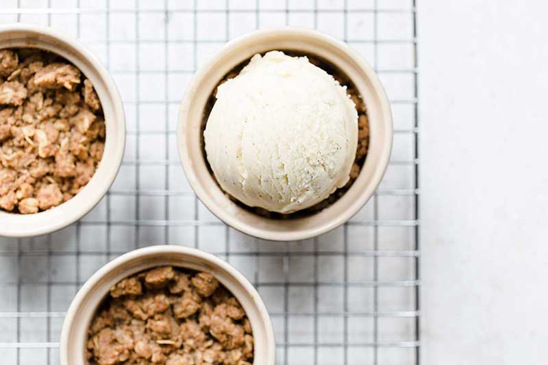 overhead photo of 3 apple crumble servings, 1 topped with ice cream