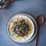 Beef stroganoff in a bowl over egg noodles