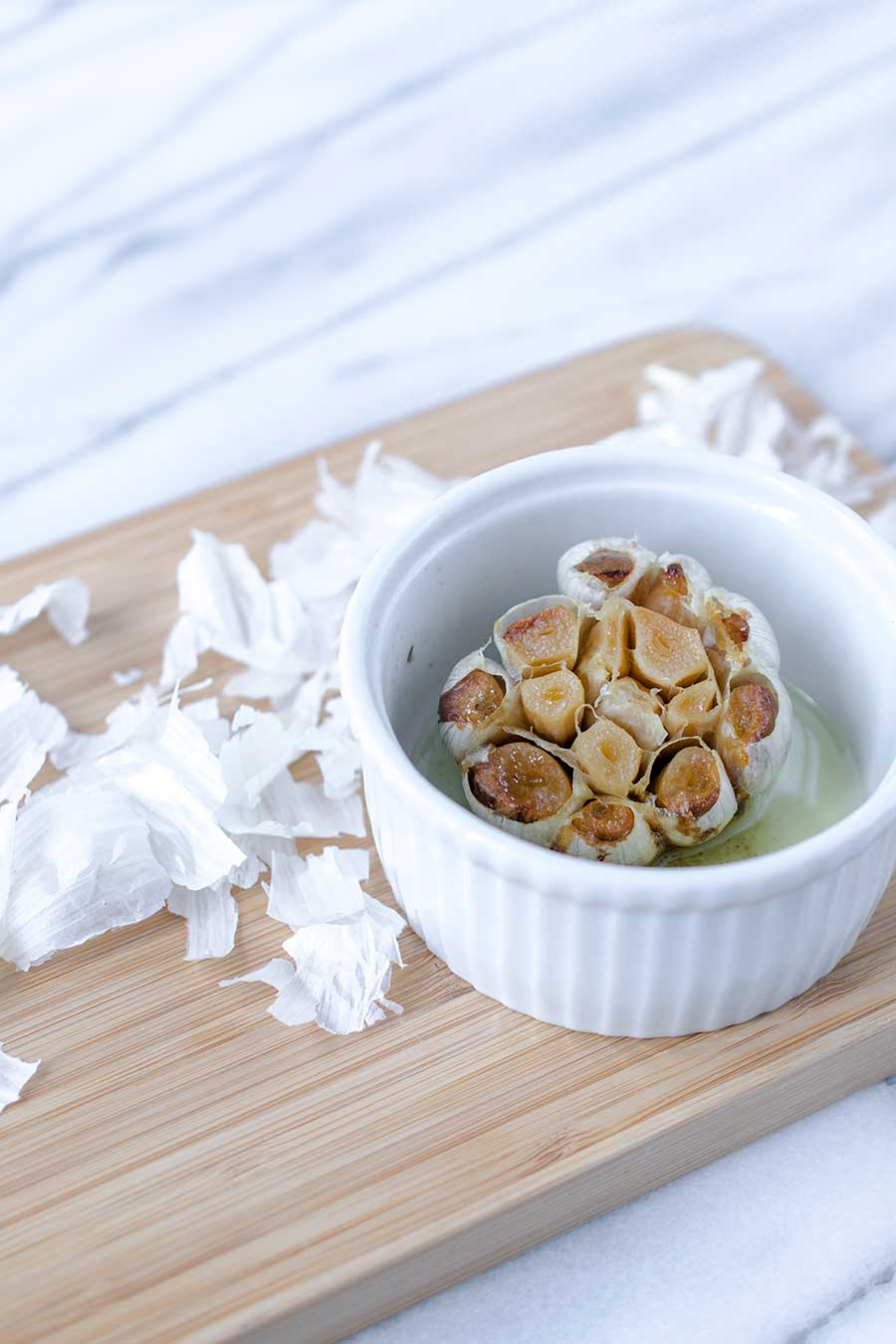 A photo of roasted garlic in a ramekin