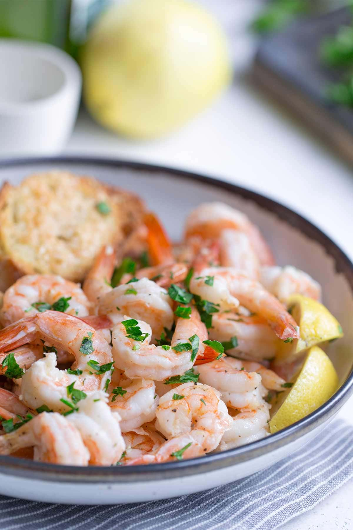 Sheet pan shrimp scampi in a bowl with bread and lemon