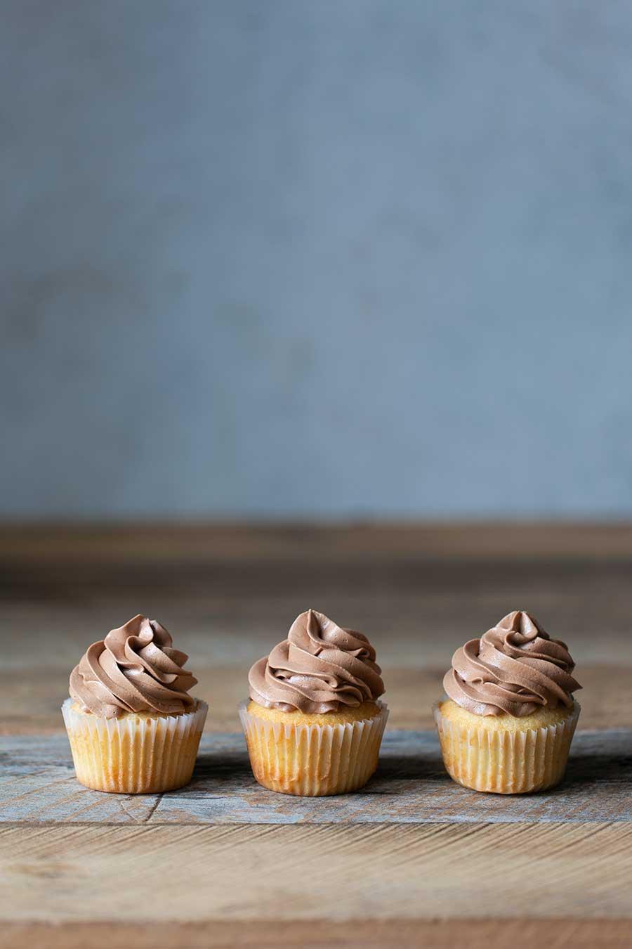 Three vanilla cupcakes with chocolate buttercream