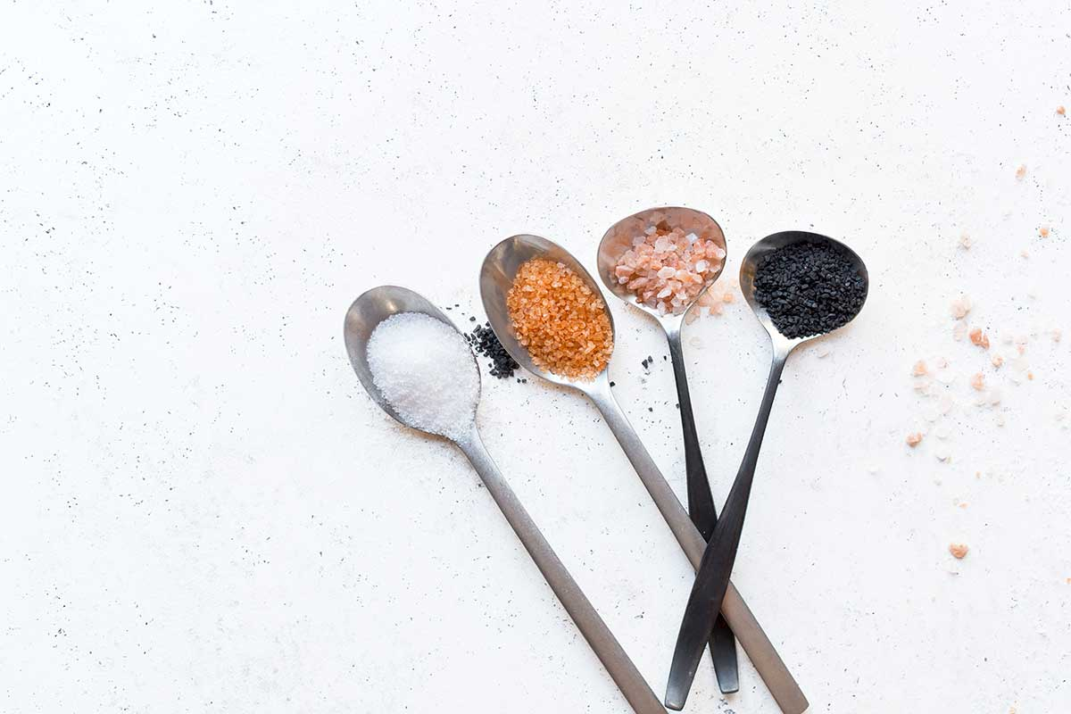 A variety of salts presented in spoons, representing one of the five tastes
