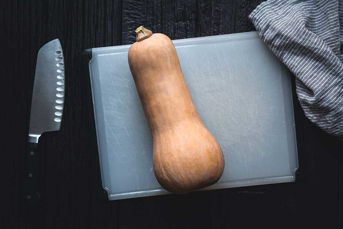 butternut squash on a cutting board with a knife