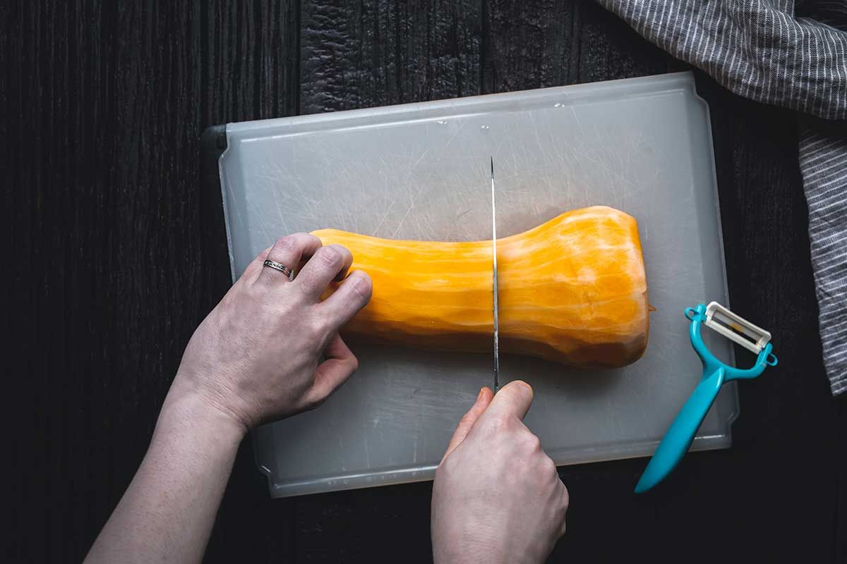 using a knife to slice one half down the center crosswise
