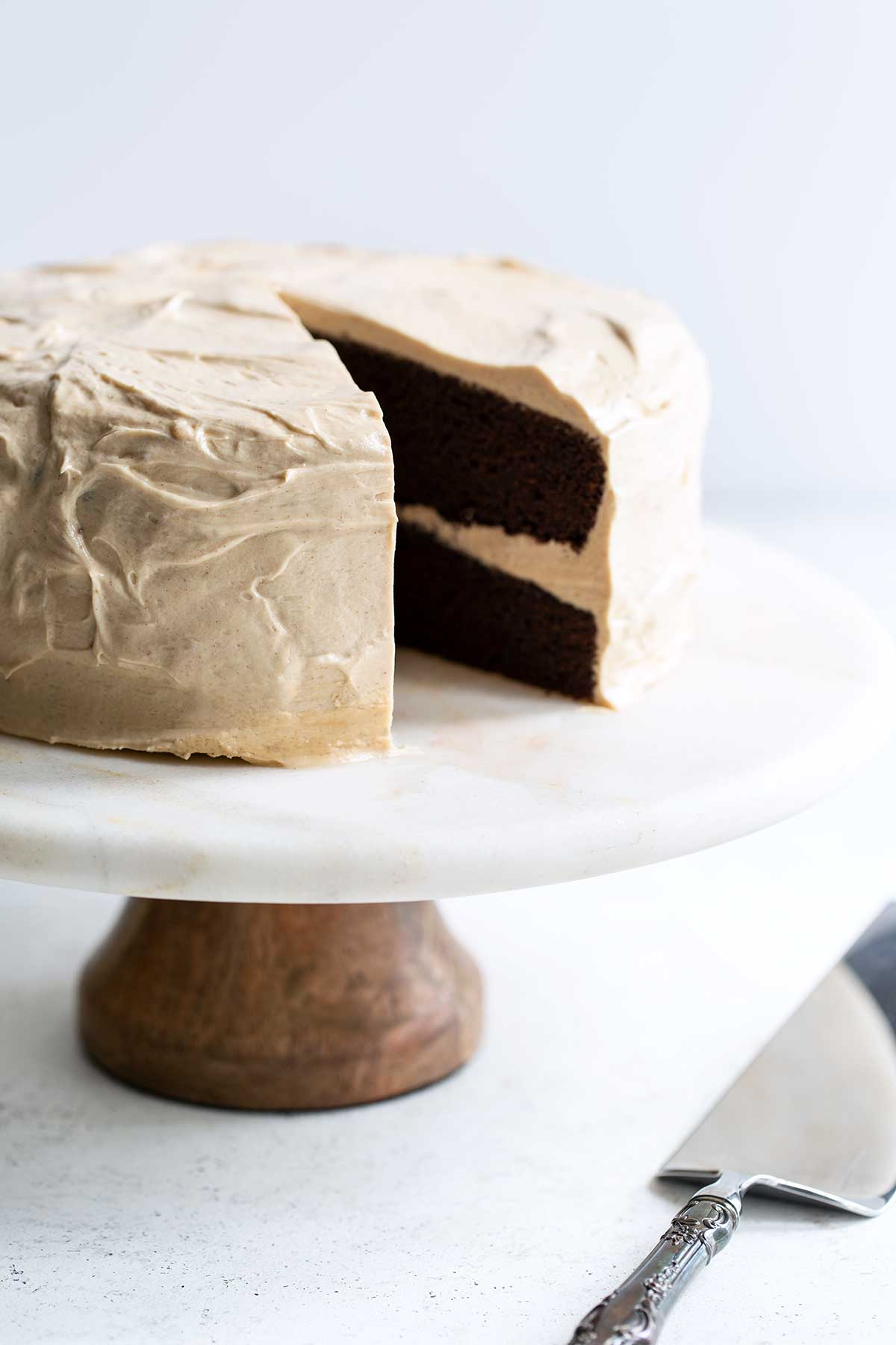 Layer cake on a cake stand with a slice missing