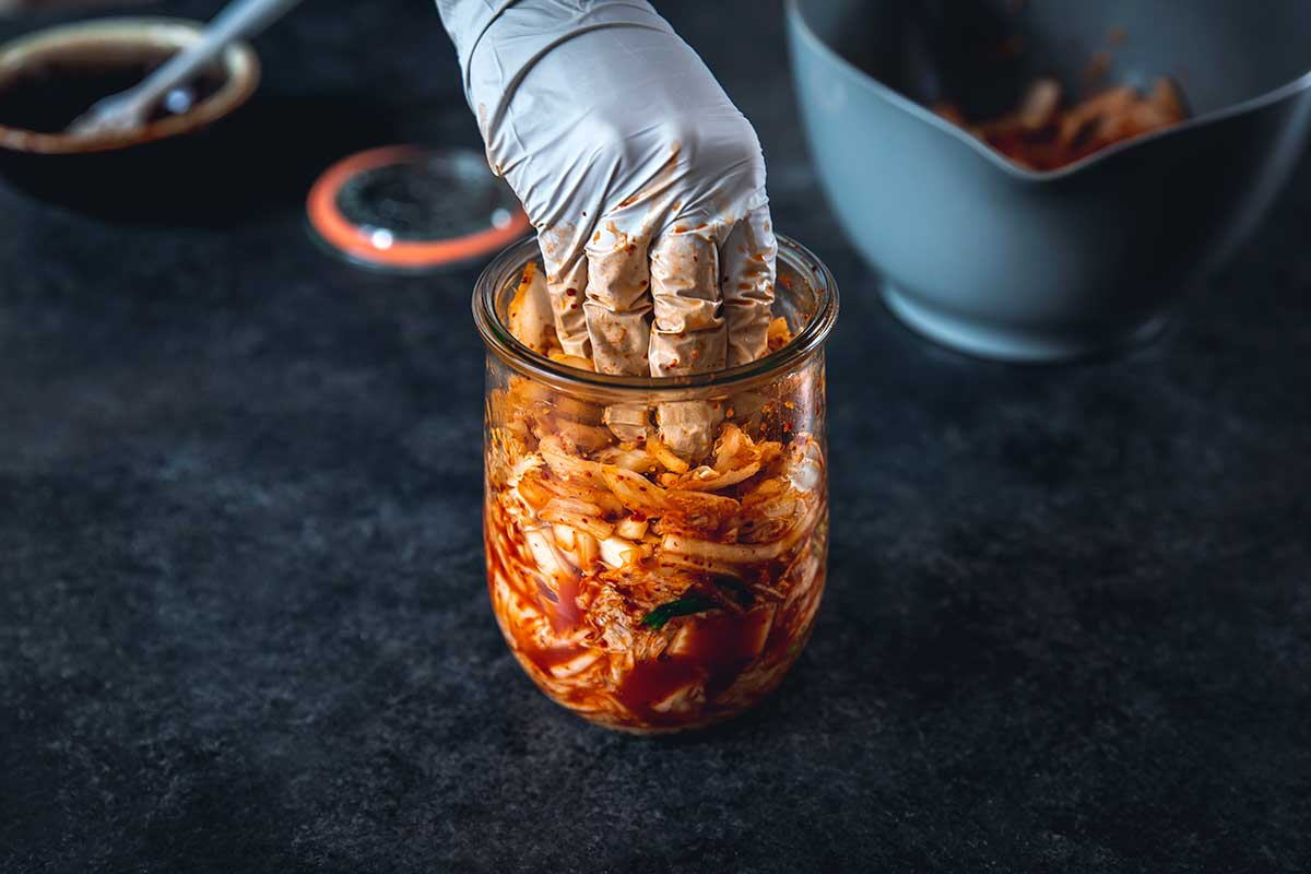 Packing kimchi in a jar to ferment