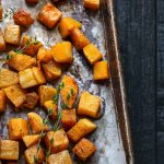 Roasted butternut squash on a sheet pan topped with thyme
