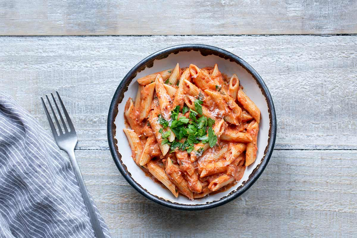 Penne with Vodka Sauce in a bowl with napkin and fork to the left