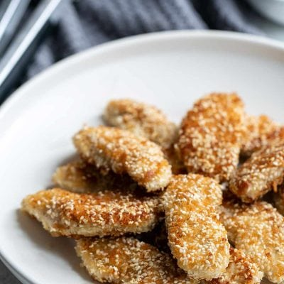 A combination of sesame seeds and panko breadcrumbs makes these chicken fingers incredibly crunchy! The peanut dipping sauce pairs perfectly.