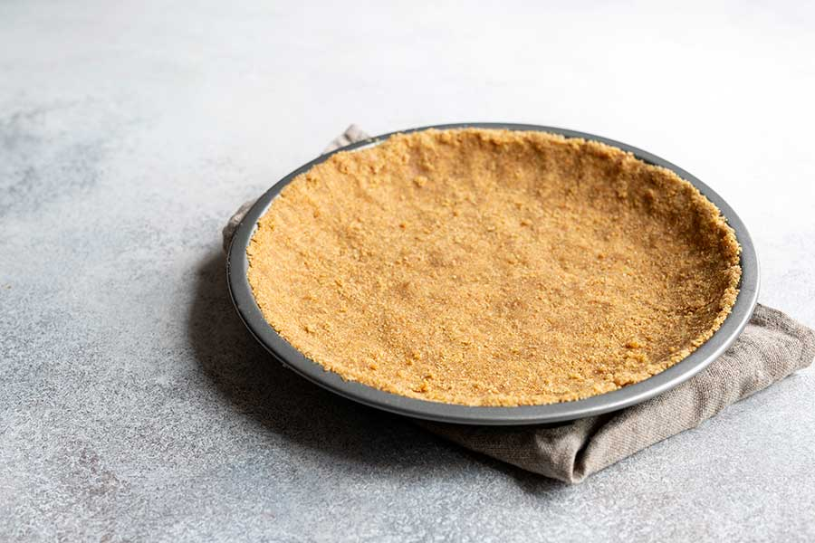 Unbaked graham cracker crust that's been pressed into a pie dish