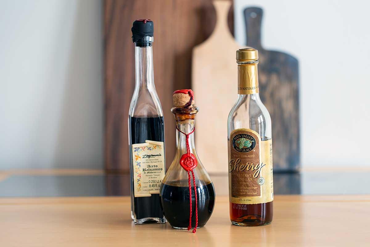 3 bottles of vinegar on a table