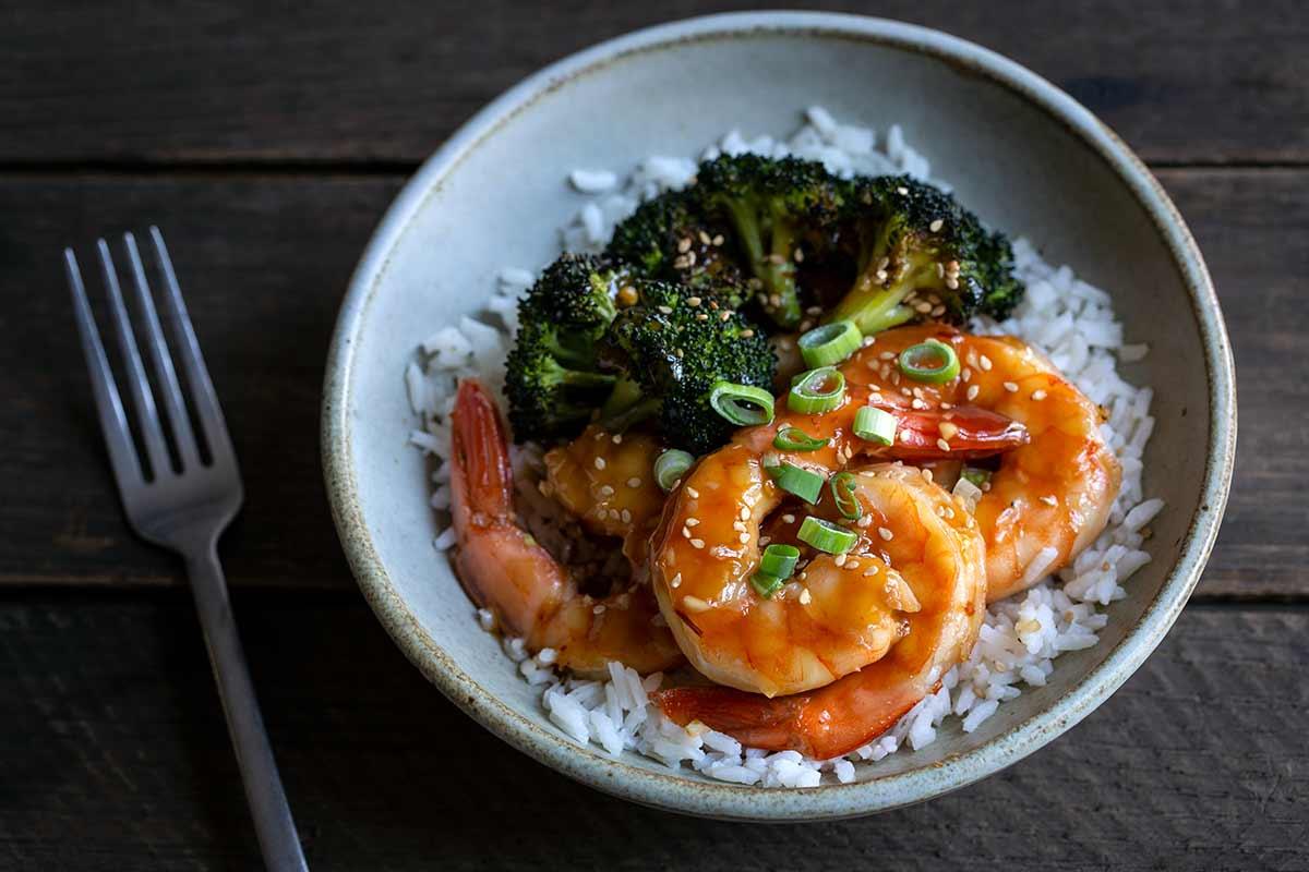 Honey garlic shrimp with fork on the left